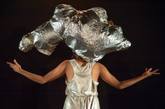 photo of performer Priya Mistry in a sparkly dress with a silver balloon across her head