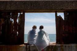 Two people partaking in the Last Resort sit in a dilapidated window frame overlooking the sea.