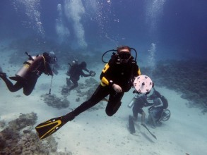 Divers underwater: In foreground Trish holds the 360 rig, Sue in chair in background with other divers
