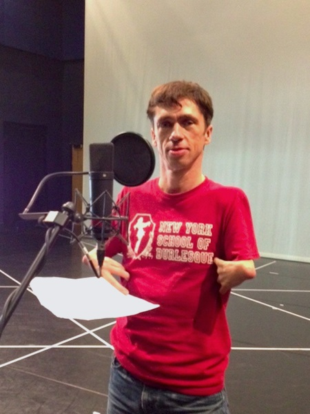 photo of actor mat fraser wearing a red t-shirt as he records audio-desciption for In Water I'm Weightless