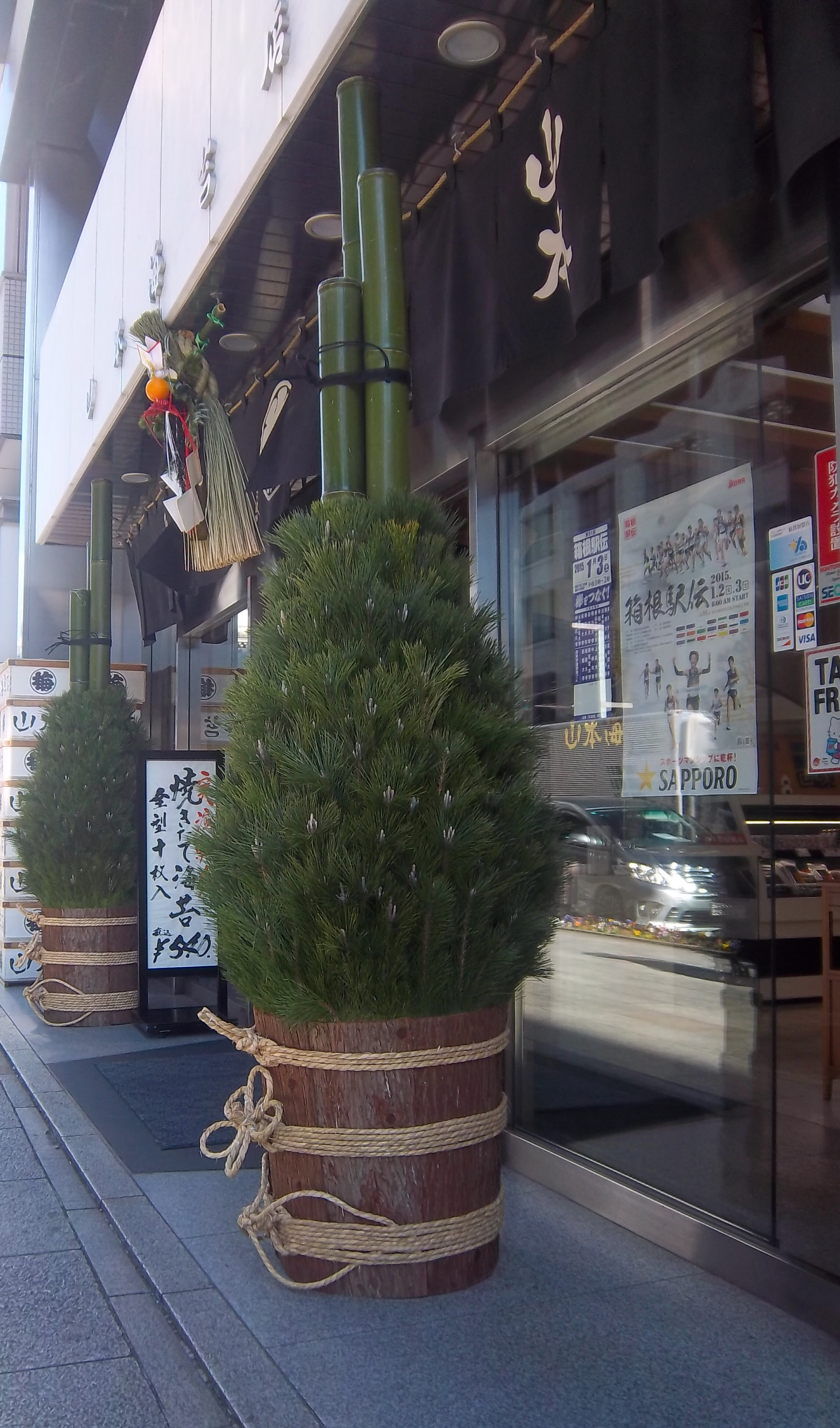 a pair of Kadomatsu, traditional New Year symbolic decoration of pine branches, bamboo and straw standing out side the entrance to a shop, flanking a corn dolly style message above the door.