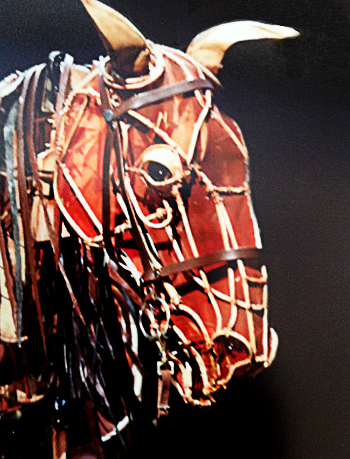 a close-up image of the warhorse head in chestnut brown against a black background. The external framework is clearly visible, with a leather bridle and an open, lifelike eye